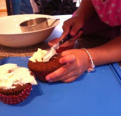 Putting icing on a red velvet cupcake